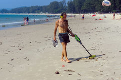 Treasure hunter with Metal detector on the beach Stock Images