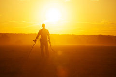 Treasure hunter. With Metal detector in the field on the sunset Royalty Free Stock Photography