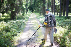 Treasure hunter with metal detector. And shovel in forest Royalty Free Stock Image