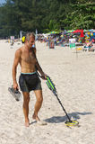 Treasure hunter with Metal detector on sunny day  the beach Royalty Free Stock Photos