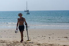 Treasure hunter with Metal detector on sunny day  the beach Royalty Free Stock Image