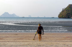 Treasure hunter with Metal detector on sunrise the beach Stock Images