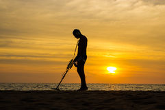 Treasure hunter with Metal detector on sunset the beach. A treasure hunter with Metal detector on sunset on the beach Royalty Free Stock Images