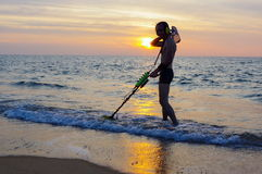 Treasure hunter with Metal detector on sunset  the beach Royalty Free Stock Images