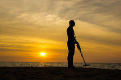 Treasure hunter with Metal detector on sunset  the beach Royalty Free Stock Photos