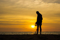 Treasure hunter with Metal detector on the sunset the beach. A treasure hunter with Metal detector on sunset on the beach Royalty Free Stock Photos