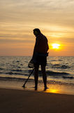 Treasure hunter with Metal detector on sunset the beach. A treasure hunter with Metal detector on sunset on the beach Stock Images