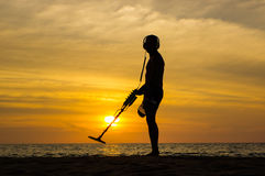 Treasure hunter with Metal detector on sunset the beach. A treasure hunter with Metal detector on sunset on the beach Stock Photo