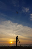 Treasure hunter with Metal detector on the sunset the beach,  a plan in the sky. Royalty Free Stock Photo