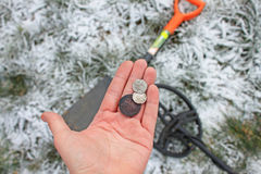 Treasure hunter. Searching with metal detector. Old Coins in hand Royalty Free Stock Images