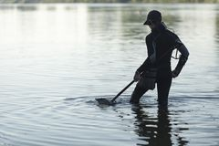 Treasure hunter is looking for a metal detector in the river. Treasure hunter treasure hunter is looking for a metal detector in the river Royalty Free Stock Photos