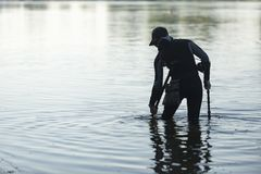 Treasure hunter is looking for a metal detector in the river. Treasure hunter treasure hunter is looking for a metal detector in the river Royalty Free Stock Images