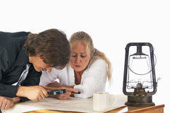 Treasure Hunters. Two modern treasure hunters study a topo map to find clues to the location of valuable treasure. Isolated on a white background Stock Image
