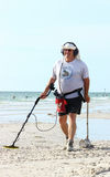 Treasure Hunting at the Beach. A man using a metal detector at the beach to look for valuables stock photo