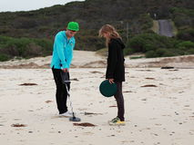 Friends on treasure hunt at beach. Young adults on a hunt with detector and container at a beach in Australia. Leisure time activities royalty free stock photos