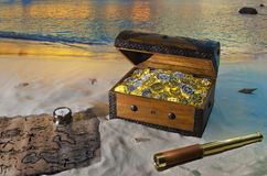 Treasure Island. Antique spyglass, treasure map and pirate chest filled with gold and silver coins on the beach at sunset stock image