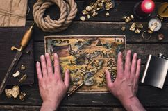 Treasure map in adventurer treasure hunter hands. royalty free stock image
