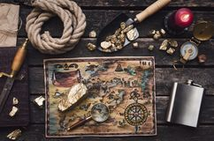 Treasure map. Old treasure map on adventurer or pirate table. Gold nuggets in shovel, compass, dagger, magnifying glass, rope and diary book on explorer desk stock photo