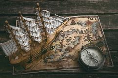 Treasure map. Pirate ship, treasure map and a compass on a wooden table background royalty free stock images
