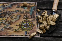 Treasure map and gold. Treasure map and shovel full of gold nuggets ore on wooden table. Treasure hunter or gold miner concept stock photo