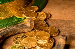 Pile of gold coins from green hat St Patricks Day. Treasure of pure gold coins from a green hat on rustic wooden table into horseshoe to celebrate luck on St Royalty Free Stock Photos