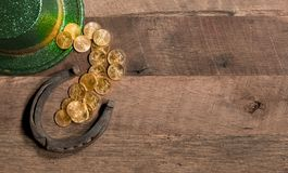 Pile of gold coins from green hat St Patricks Day. Treasure of pure gold coins from a green hat on rustic wooden table into horseshoe to celebrate luck on St Stock Photos
