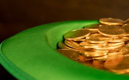 Pile of pure gold coins inside green hat St Patricks Day. Treasure of pure gold eagle coins inside the rim of a green velvet hat to celebrate luck on St Patrick` Royalty Free Stock Photos