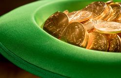 Pile of pure gold coins inside green hat St Patricks Day. Treasure of pure gold eagle coins inside the rim of a green velvet hat to celebrate luck on St Patrick` Stock Photos