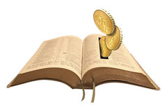 Treasures in heaven bible. Concept photo of gold coins being deposited into open pages of bible depicting theme of treasures in heaven,donations etc Royalty Free Stock Photos