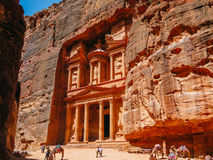 The Treasury in Petra. Literally carved directly into vibrant red, white, pink, and sandstone cliff faces, the prehistoric Jordanian city of Petra was once a Stock Photography