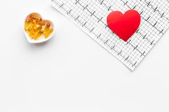 Treat heart. Pills in bowl in shape of heart and cardiogram on white background top view copyspace Royalty Free Stock Photo