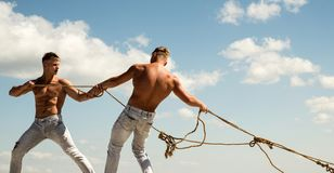 Treating your team like a family. Strong men pull ropes. Athletic twins with fit body. Twins men use muscular hand. Strength. Sport exercises for building royalty free stock photo
