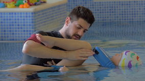 Treatment of child with exercise in water. KALIKRATIA, GREECE - JANUARY 12, 2016: Man providing treatment exercises for a child in the pool. Therapy course in stock footage