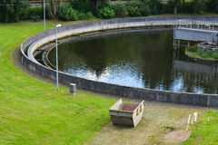 Treatment clean. Part of round sewage treatment plant filled with Water, during Summer with Tree and surrounded by green Grass. Icon for Nature, Environment Royalty Free Stock Photography