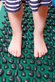 Treatment of flatfoot with massage mat. Treatment of flatfoot in young children with massage mat. Close-up Royalty Free Stock Photo