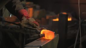 Treatment of hot metal. Blacksmith forges iron is hot. Metal forging on the anvil stock footage