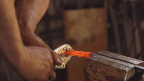 Treatment of molten metal close-up. Handmade blacksmith. Man forms a pattern on the iron clamped in the vice. slow. Blacksmith forges on the anvil. Brutal man stock footage