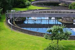 Treatment Plant. Part of round sewage treatment plant filled with Water, during Summer with Tree and surrounded by green Grass. Icon for Nature, Environment Stock Image