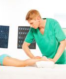After treatment specialist doing massage of feet Stock Photos
