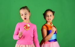 Treatment and sweets concept. Children eat big colorful sweet caramels. Sisters with round and long shaped lollipops. Girls with funny faces pose with candies Royalty Free Stock Photo