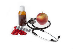 Treatments with stethoscope. Treatments with apple and stethoscope on isolated background Royalty Free Stock Images
