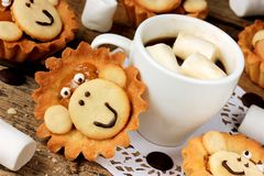 Treats on a children`s holiday, homemade cake shaped monkey, cre Stock Photos