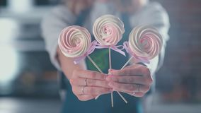 Treats on a stick in the hands of women. Woman holding three treats. Treats on a stick in the hands of women. Woman meringue pastry treats. Refreshments stock footage
