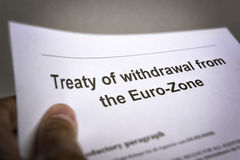 Treaty withdrawal from Euro-Zone. Man holding an treaty on the withdrawal from the euro zone in the hand Stock Images