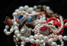Treausures from India. Chains and rings. Pearl chains and rings with coloures glass such as Swarovsky look liked as rubin and sapphire. From India stock photography