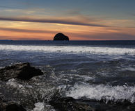 Trebarwith Strand. Near Tintagel, Cornwall, with Gull Rock in silhouette. Simulated sunset royalty free stock photography