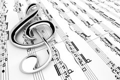 Treble clef. Chrome treble clef on sheet music Stock Photo