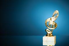 Treble clef symbol trophy on blue background Stock Photo