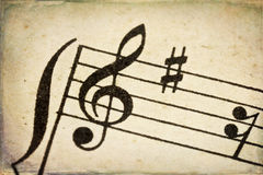 Treble clef on vintage music sheet. Treble clef - macro of sheet music on vintage paper with added grunge texture and border Stock Photography
