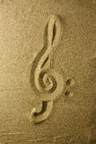 Treble clef Written in the Sand. Golden colors Royalty Free Stock Photos